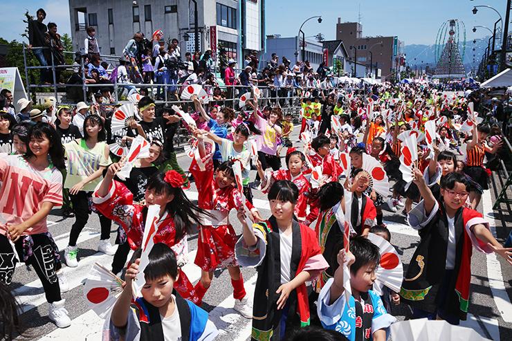 扇子を手にして「よっしゃ来い!!CHOUROKU」の総踊りを披露する参加者=魚津駅前の大通り