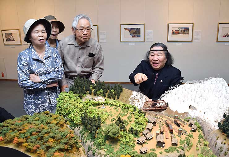 絵本「さだおばさん」の世界を表現した模型を来場客に解説する原田さん(右)