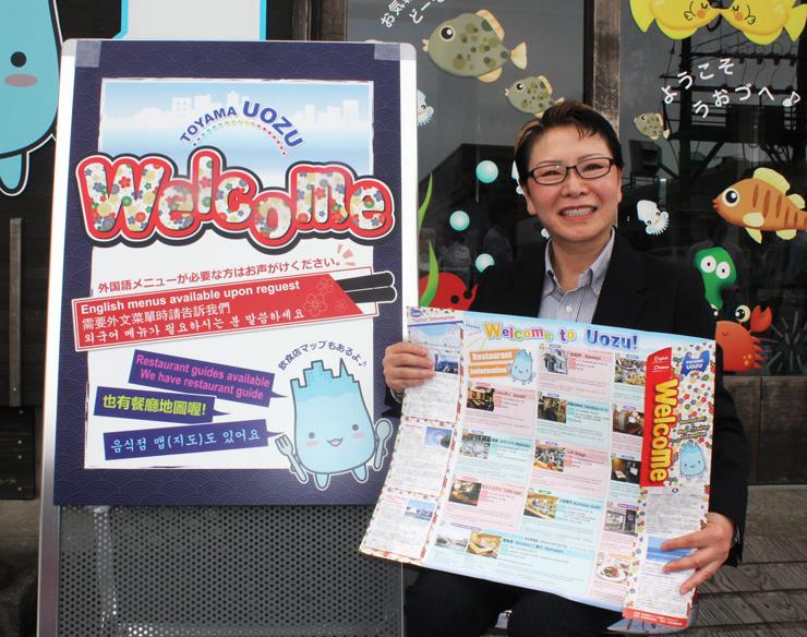 ガイドマップを手にする水田組合長。左は紹介店に設置する外国語表記の看板=魚津駅前観光案内所