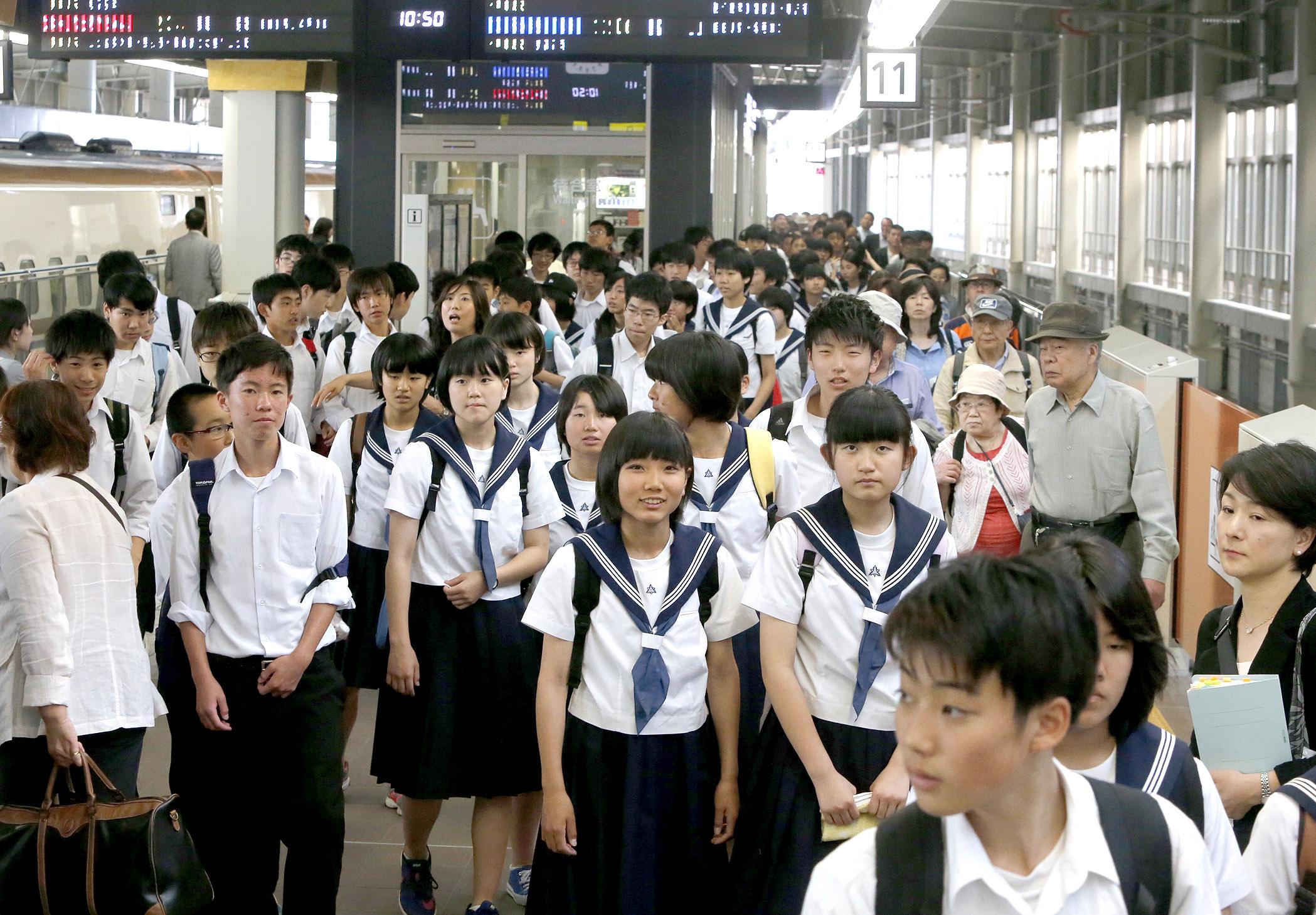 北陸新幹線を利用して修学旅行に訪れ、笑顔でホームを歩く船橋中の生徒=20日午前10時50分、JR金沢駅