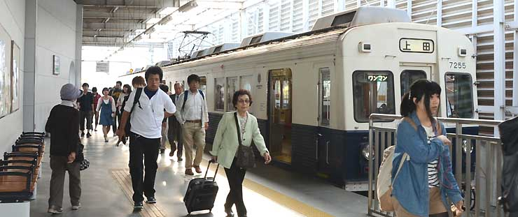 別所線上田駅に到着した電車を降りる乗客。北陸新幹線やしなの鉄道に乗り換える乗客も多い=20日