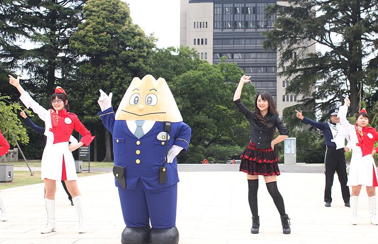 県警本部をバックに、「立山くん」とのダンス動画を撮影するぶらっくすわんさん(右から3人目)=富山城址公園