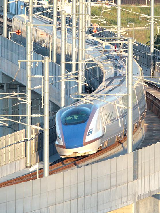 富山駅に向かう北陸新幹線=21日、富山市の呉羽山から撮影