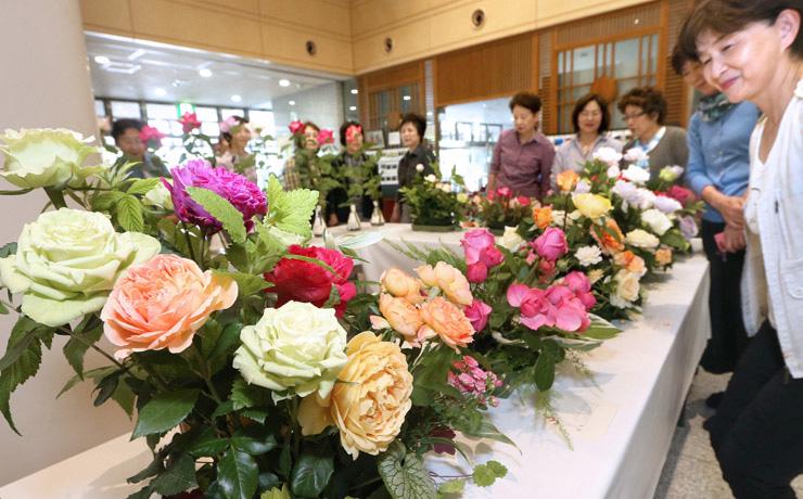 気品あふれるバラに見入る来場者=23日午前10時50分、金沢市の本多の森ホール