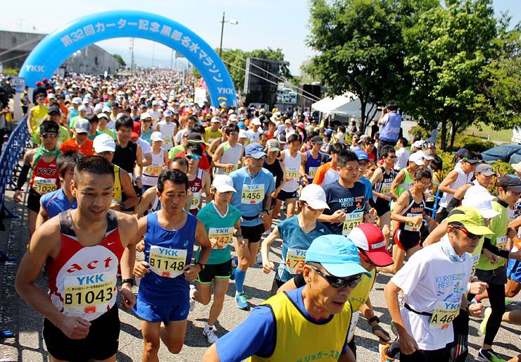 一斉にスタートするフルマラソンの出場者=黒部市総合公園前