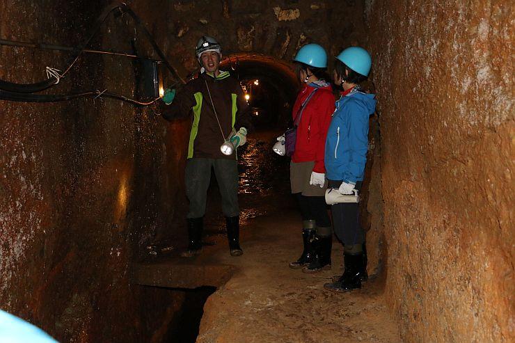 山師コースで南沢疎水道を案内する岩見昭一郎さん(左)。当時の手作業の様子が見て分かるという=佐渡市