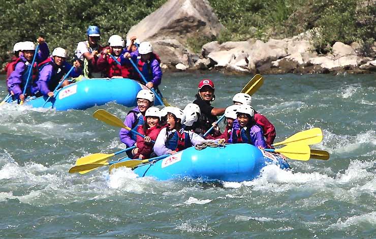 水しぶきを浴びながらボートに乗って天竜川を下る中学生たち