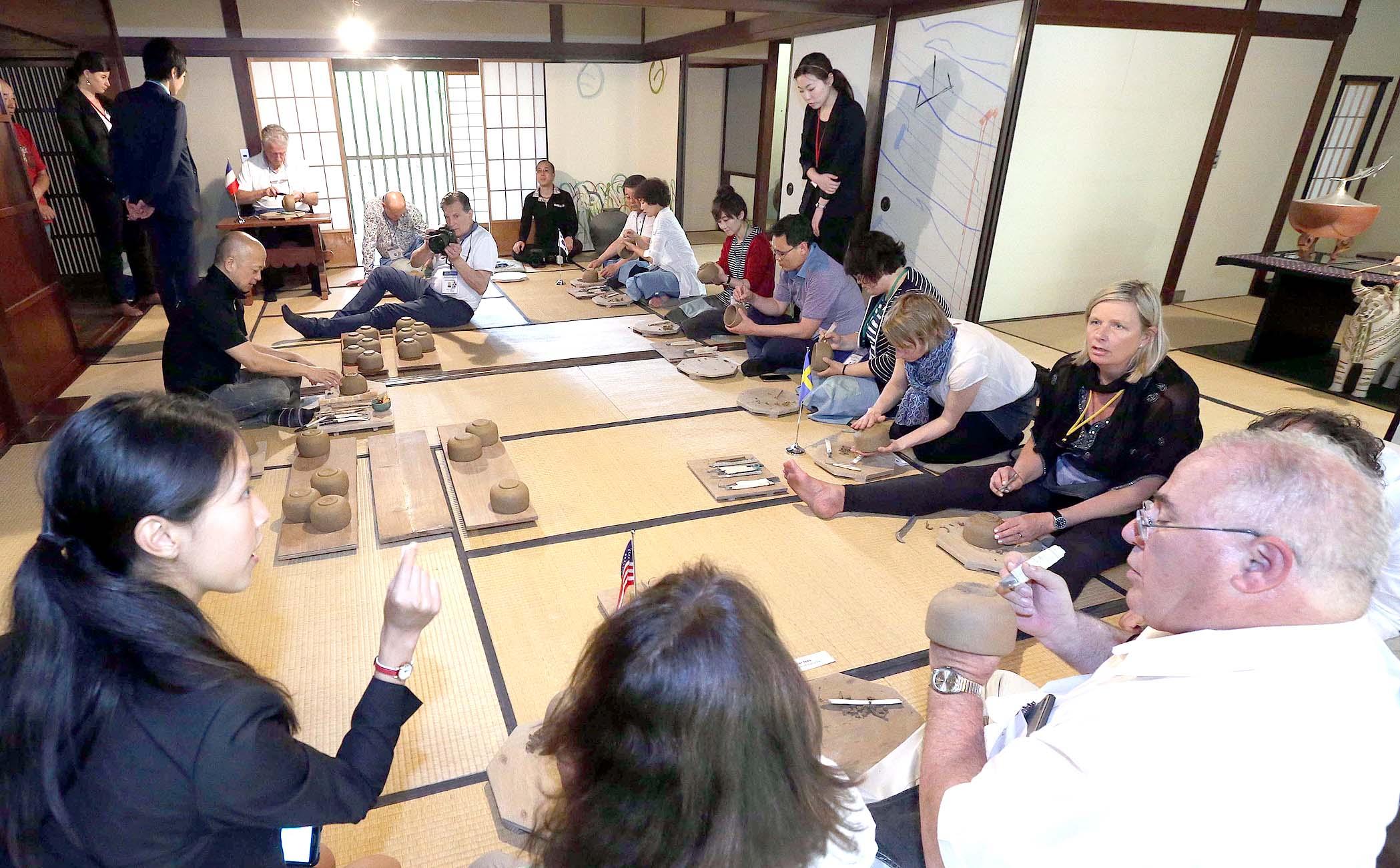 作陶を体験する世界会議の出席者=28日午前11時40分、金沢市舘町