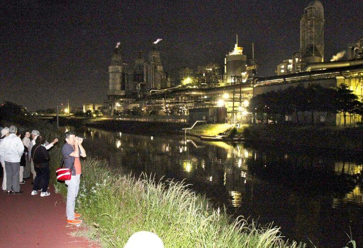 幻想的な雰囲気が漂う旭カーボンの工場夜景に見入るツアーの参加者=新潟市東区