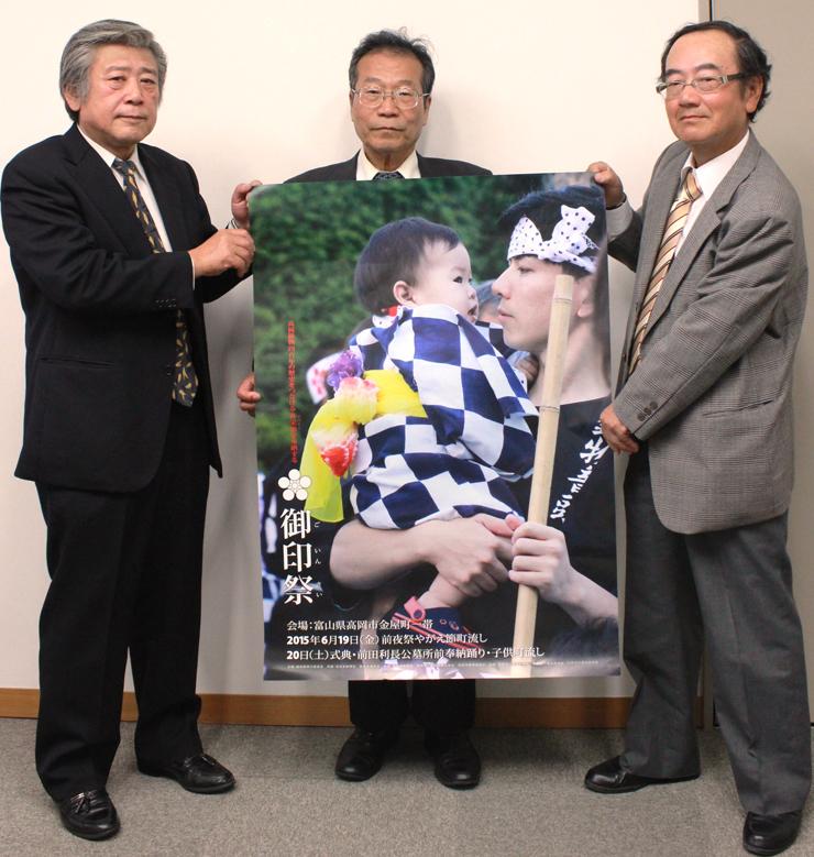 御印祭のポスターを手にする(左から)加藤顧問、田子会長、松原事務局長=北日本新聞高岡支社