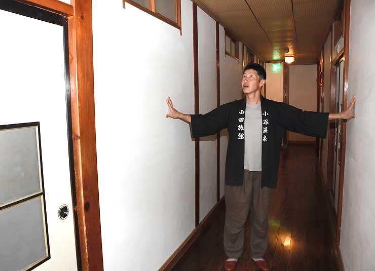 補修が終わった壁の仕上がりを確かめる山田さん