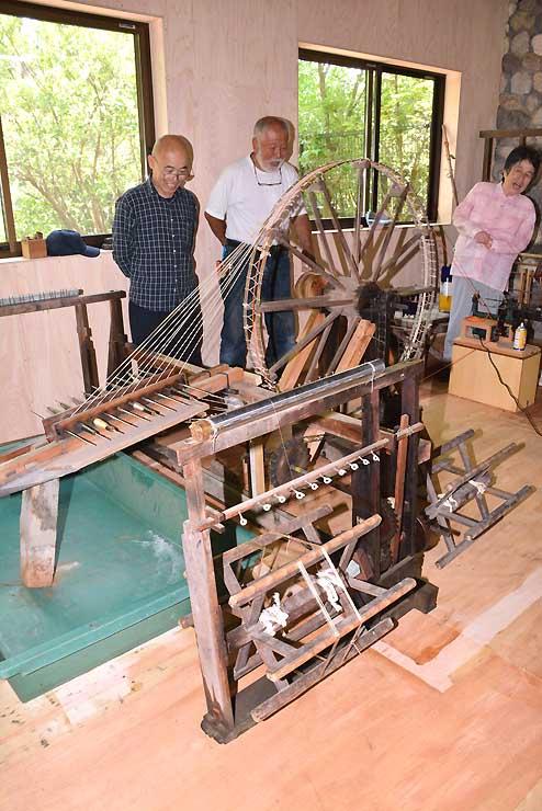 昔ながらの「八丁撚糸機」を約30年ぶりに動かし、笑顔を見せる関係者