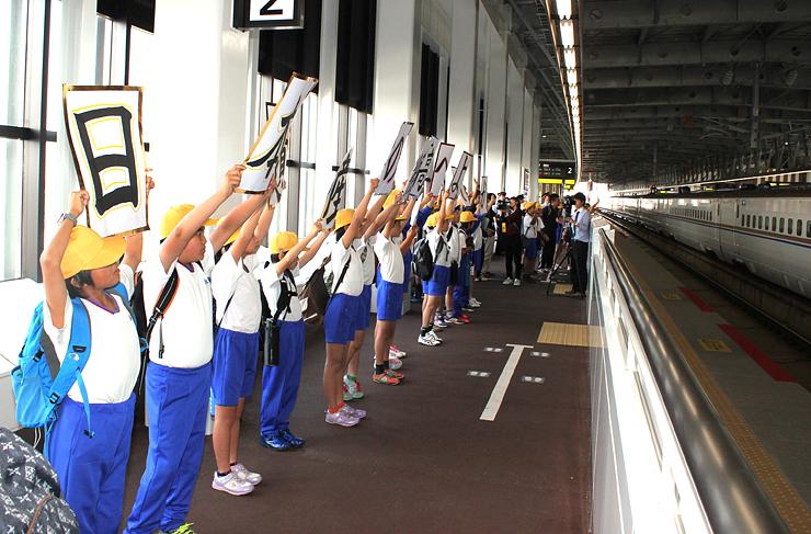 向かい側のホームから出発する「はくたか」にボードでメッセージを送る児童=北陸新幹線新高岡駅