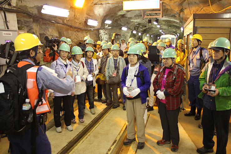 関西電力の社員から竪坑エレベーター前で説明を受ける参加者