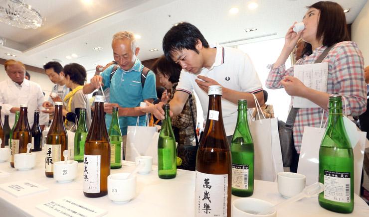 利き酒を楽しむ来場者=30日午前11時5分、金沢市のしいのき迎賓館