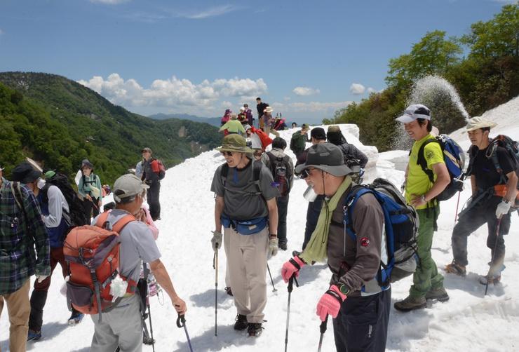 白馬大雪渓に到着し、笑顔で涼風を楽しむ参加者=30日、白馬村