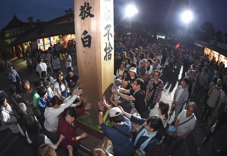 夜になってからも大勢の参拝客でにぎわう回向柱の周辺=30日午後7時26分、長野市の善光寺本堂前(対角魚眼レンズ使用)