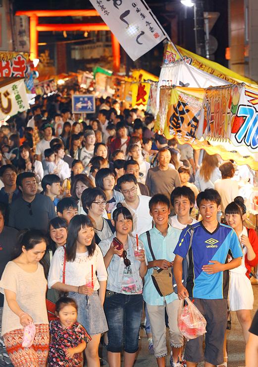 日枝神社前に並んだ露店を眺めながら歩く大勢の人たち=富山市西町