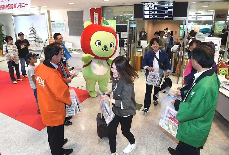 福岡線で到着し、FDA就航5周年の記念品を受け取る利用客=1日正午、松本空港