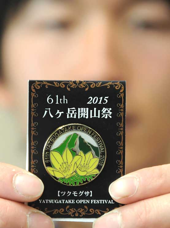 開山祭の参加者に贈る「ツクモグサ」のピンバッジ