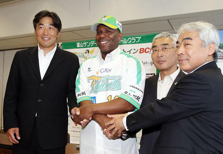 ユニフォームにそでを通し、笑顔を見せるローズ選手(右)と吉岡監督=高岡市役所