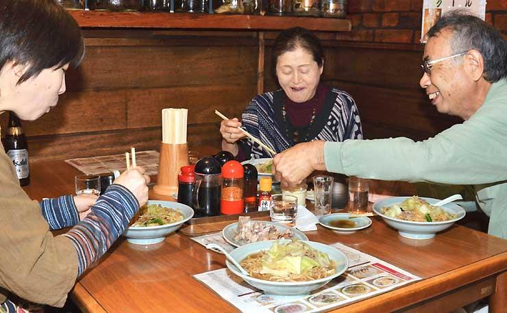 談笑しながら萬里本店でローメンを食べる家族