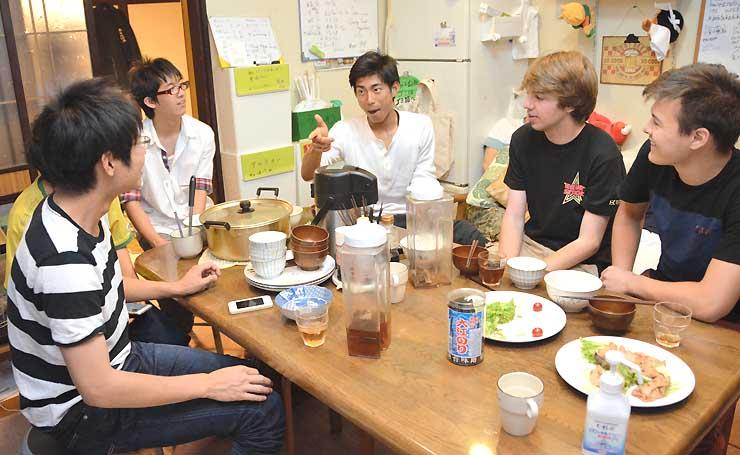 夕食後に下宿の食堂で米国人大学生の旅行客と話す信州大の下宿生たち=2日夜、松本市