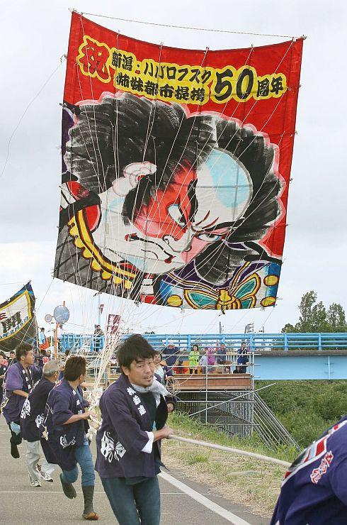 堤防を駆け24畳の大凧を揚げた白根大凧合戦=4日、新潟市南区