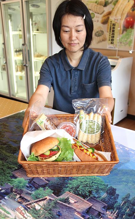大豆加工品で作った五箇山生まれのハンバーガーとホットドッグを手にする細川さん