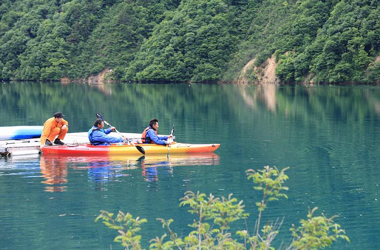 エメラルドグリーンの湖面でカヌーを体験する人々=南砺市桂