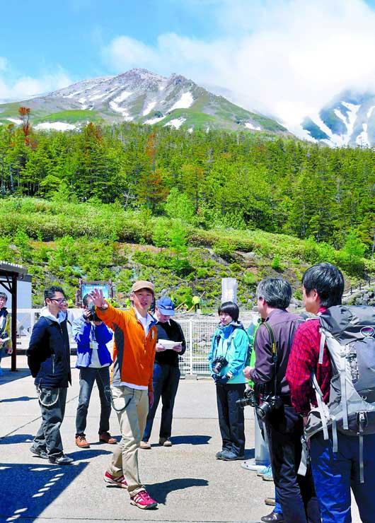 山岳ガイドの案内で、御岳ロープウェイ飯森高原駅周辺を散策する観光客ら=6日午前10時31分