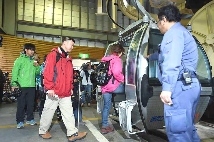 今季の運行が始まり、ゴンドラに乗り込む観光客たち=6日午前8時32分、御岳ロープウェイ鹿ノ瀬駅