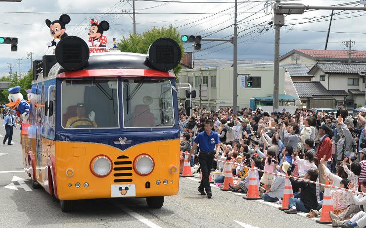 大勢の歓声を浴びてパレードするミッキーマウスらディズニーキャラクター=6日、大町市大町