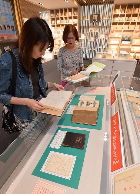 復刻版を手に秋山徳蔵の著書の原書を興味深く見る来場者=6日、福井市の県ふるさと文学館