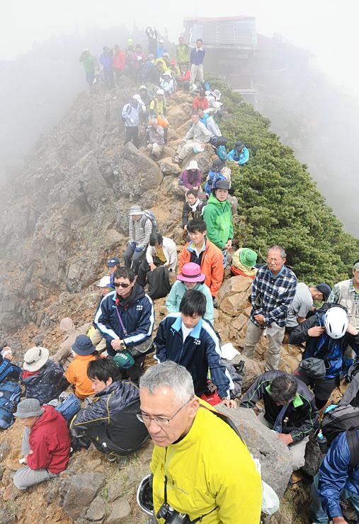 赤岳山頂の開山祭に参加し、夏山の安全を祈願する登山者たち=7日午後0時20分、赤岳
