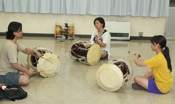 昨年8月のワークショップで張在孝(左)から韓国打楽器を学ぶ中学生ら。ことしは親指ピアノ、合唱と合同で行う