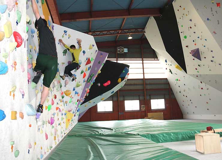 ボルダリング用の壁を登る人たち。右側はロープを付けて登る壁