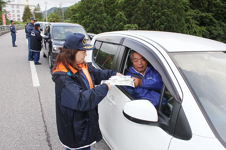 ドライバーにチラシを配る女性消防団員=富山市亀谷