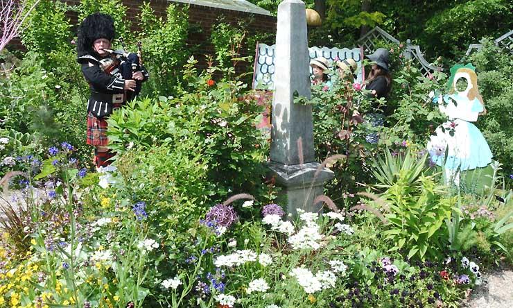 「不思議の国のアリス」を題材にした庭でバグパイプの演奏もあったフラワーショー