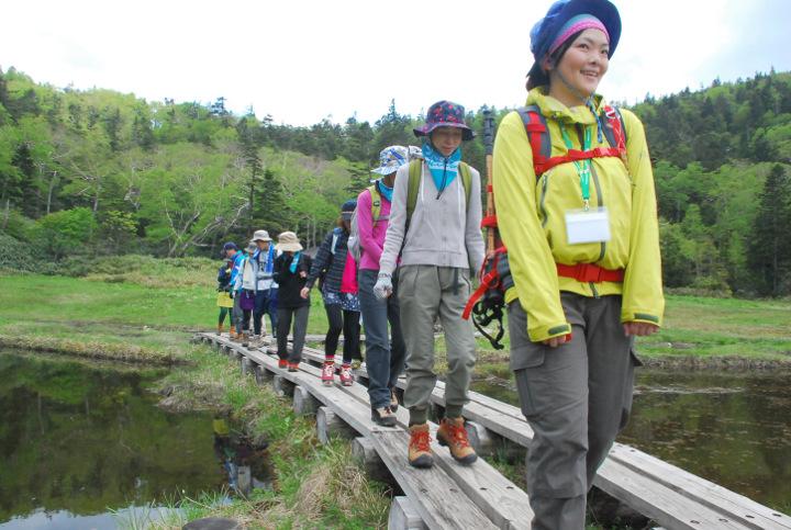 ガイドの案内で木道を歩く参加者たち
