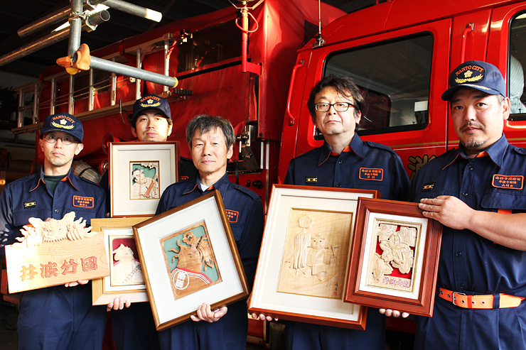 それぞれが手掛けた木彫パネルをPRする(右から)山崎さん、井口さん、高桑さん、前川さん、高田さん=南砺市消防団井波分団屯所