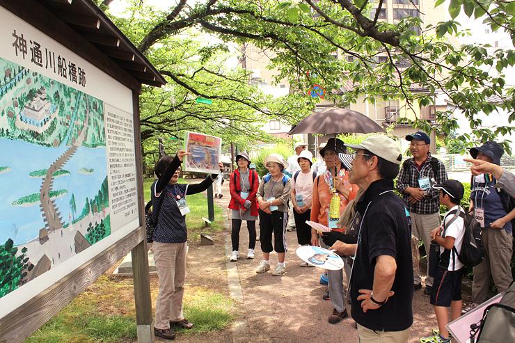 松川沿いで、かつて神通川に架かっていた舟橋についての説明を聞く参加者=富山市丸の内