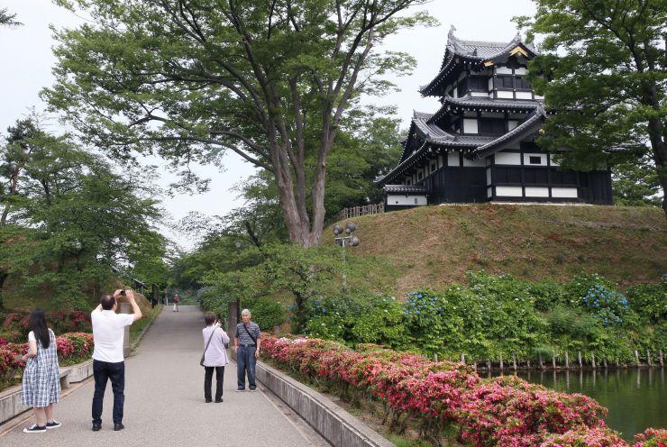 高田城三重櫓(やぐら)をバックに記念撮影する人たち。新幹線利用者をどう上越市内の観光に結びつけるかが問われている=15日、同市