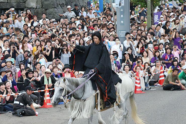 熱気に包まれた謙信公祭の会場で、上杉謙信役を演じるGACKTさん昨年の様子=2014年8月24日、上越市の謙信公通り