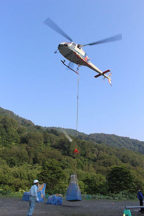 山小屋へ荷上げする資材や食料を運ぶヘリコプター=17日、胎内市