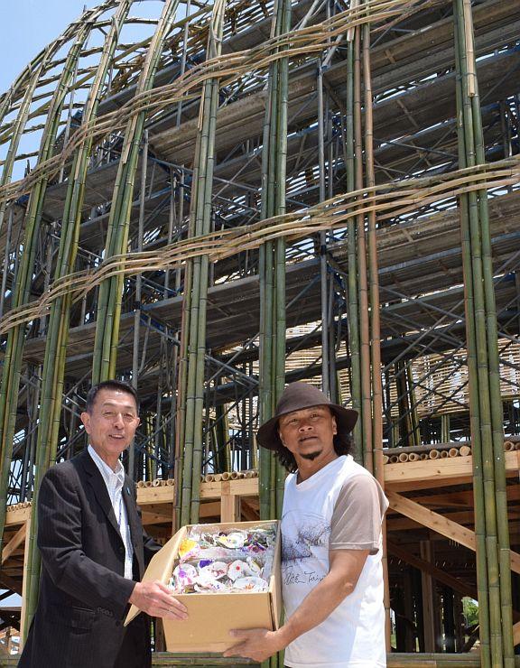 王文志さん(右)にカキ殻を手渡す篠田昭市長=17日、新潟市中央区