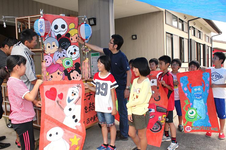 ディズニーキャラクターの絵を描いた和紙を順番に貼る児童と保護者