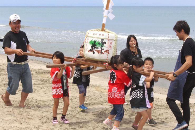 みこしを担ぎ元気よく砂浜を練り歩く藤塚浜保育園の園児ら=19日、新発田市
