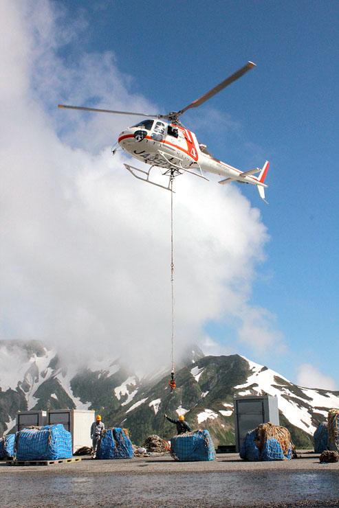 例年より雪の少ない大日連山をバックに、山小屋への物資を空輸するヘリ=国見ヘリポート