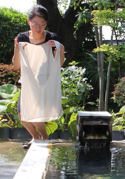 湯田上温泉旅館協同組合が独自に開発した入浴着を手にするおかみの細井久美子さん=田上町の末広館